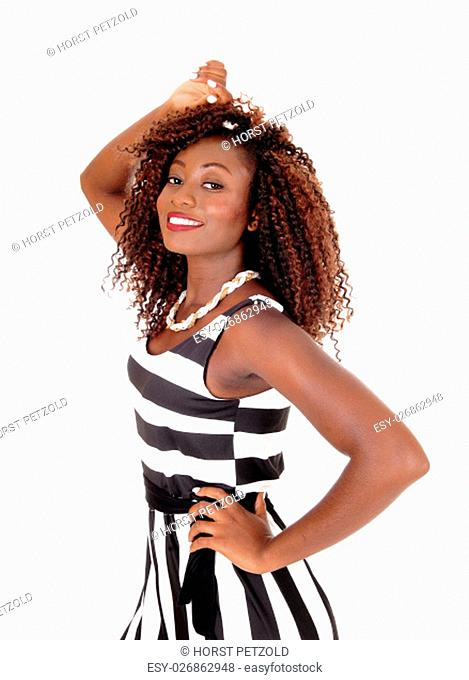 A gorgeous young African American woman standing in a black and white.jumpsuit, isolated for white background.