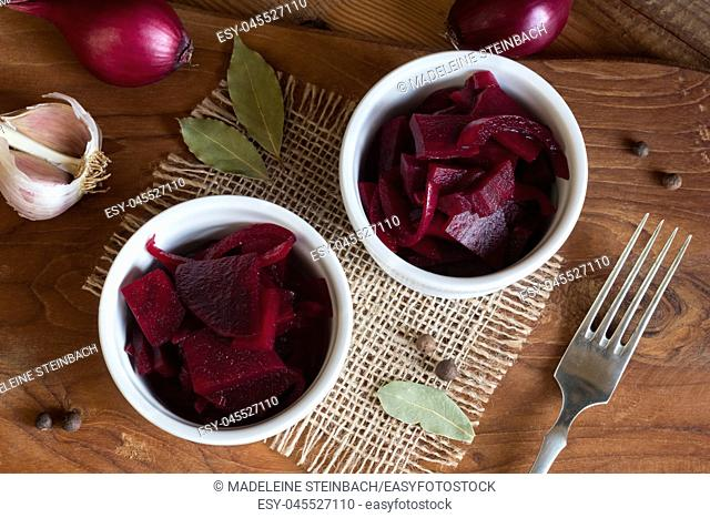 Fermented red beet with onions in two round bowls, with garlic, purple onions, allspice and bay leaf in the background, top view