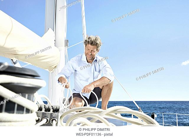Mature man working with ropes on sailing boat