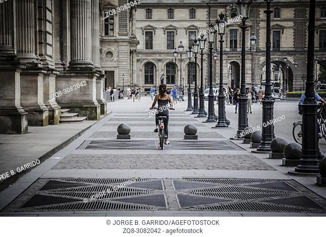 young woman riding a bicycle in Paris