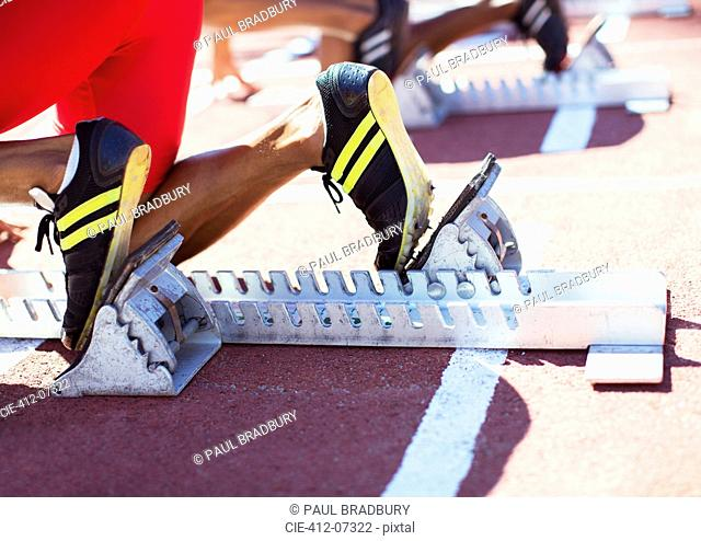 Runner's feet in starting blocks on track
