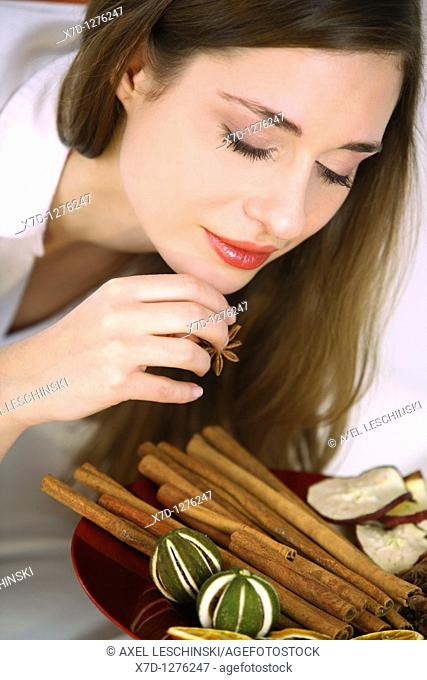 young brunette woman holding winter spices in hands