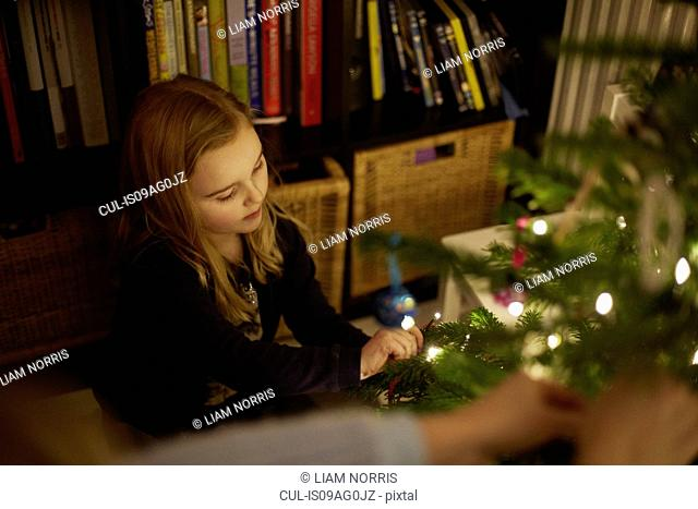 Young girl decorating christmas tree with baubles