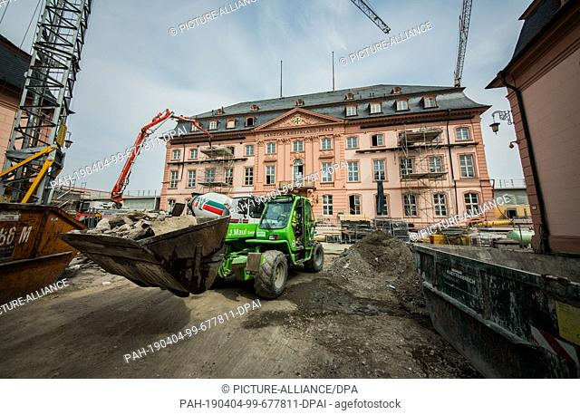 02 April 2019, Rhineland-Palatinate, Mainz: A wheel loader drives demolition stones from the Deutschhaus across the construction site