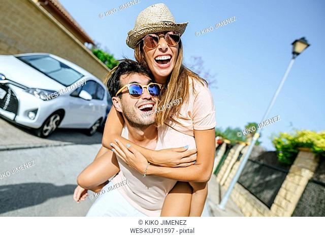 Carefree young man carrying his girlfriend piggyback