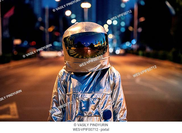 Spaceman on a street in the city at night