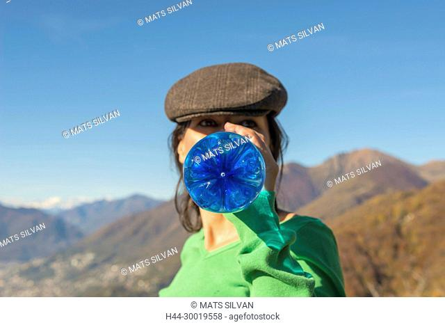 Woman With Flat Cap Drink Water From a Blue Bottle in Switzerland
