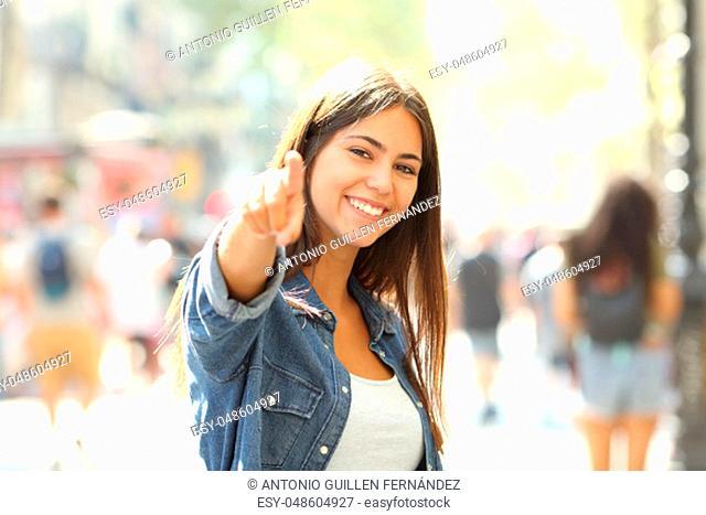 Happy teen pointing at camera inviting you