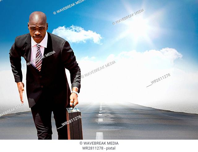 Business man running with briefcase on road against sky with sun
