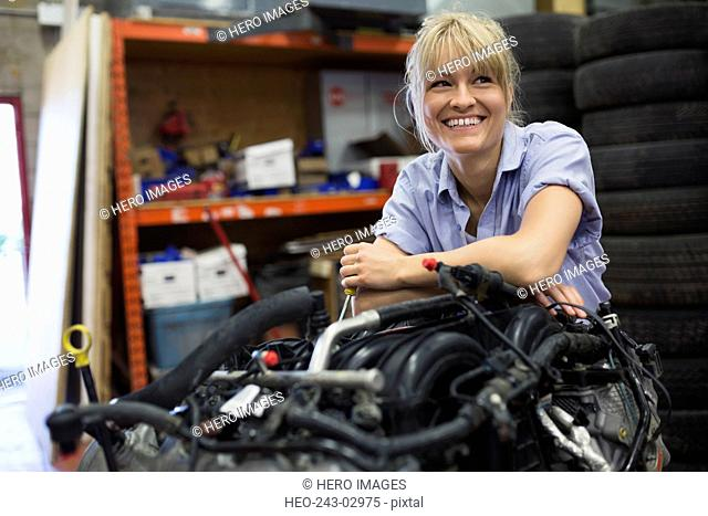 Portrait confident female mechanic leaning on engine