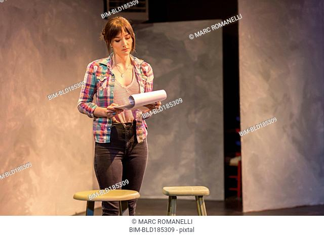 Hispanic actress rehearsing on theater stage