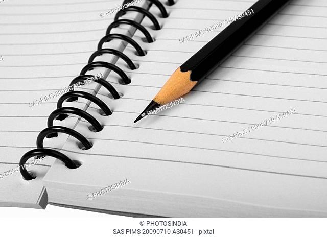Close-up of a pencil on a spiral notebook
