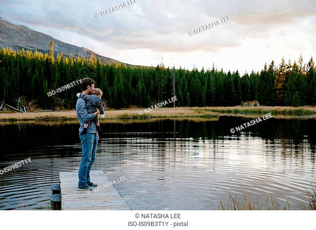 Father standing on wooden pier beside lake, holding young son
