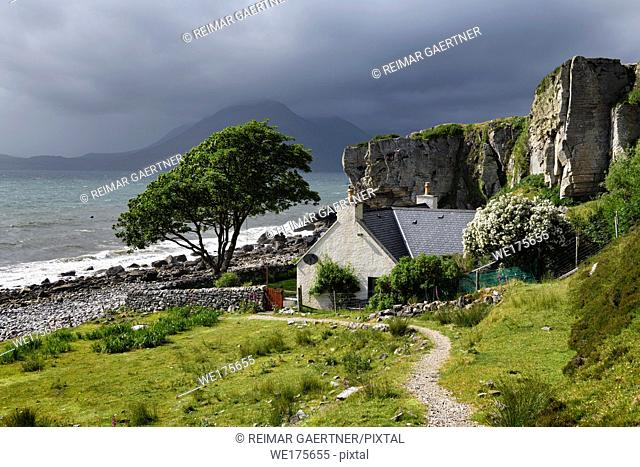 House under cliff at Elgol beach with Red Cuillin Mountains under clouds at Loch Scavaig Scottish Highlands Isle of Skye Scotland UK