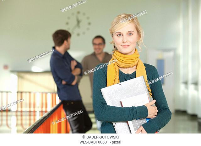 Germany, Leipzig, Young woman holding book with students standing in background