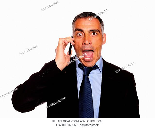 Portrait of a surprised business man on cellphone against white background