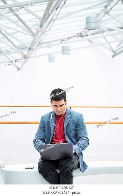 Businessman in lobby of a modern building, using