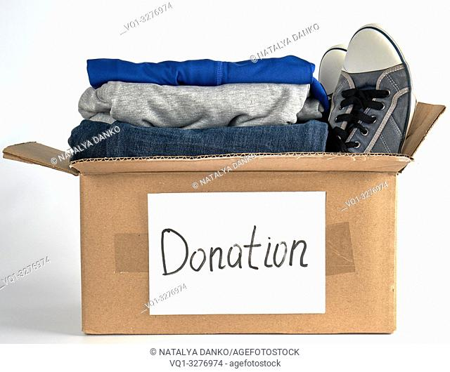 folded clothes in a brown paper box with the inscription donation on a white background, the concept of helping people in need