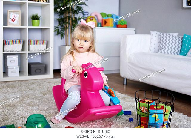 Portrait of little girl sitting on pink rocking horse in the living room