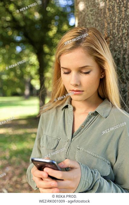 Germany, Duesseldorf, park, young woman using smartphone