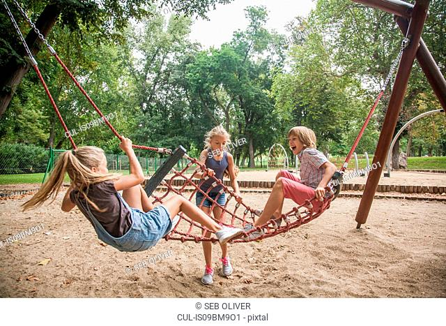 Children playing on net swing