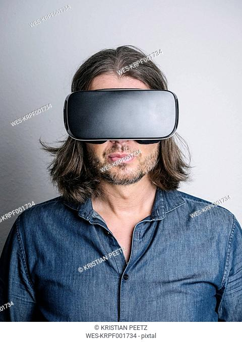 Portrait of man wearing Virtual Reality Glasses in front of grey background