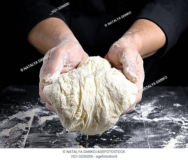 men's hands holding a ball of white yeast dough over the table