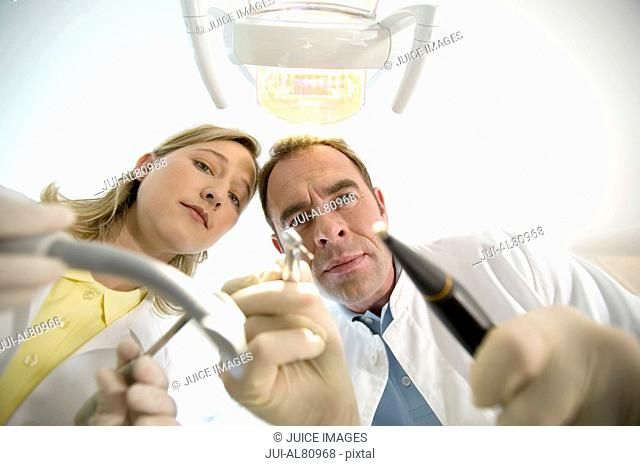 Dentist and dental assistant holding dental tools