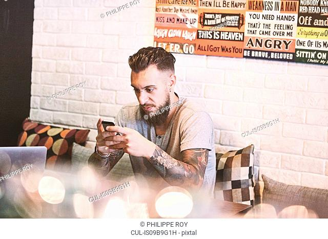 Young male hipster in cafe looking at smartphone, Shanghai French Concession, Shanghai, China