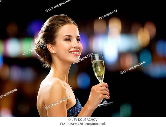 party, drinks, holidays, people and celebration concept - smiling woman in evening dress with glass of sparkling wine over night lights background