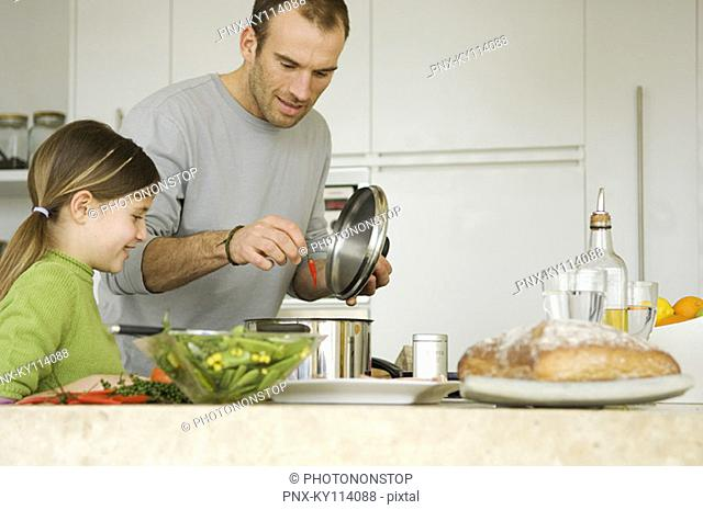 Man and girl in kitchen