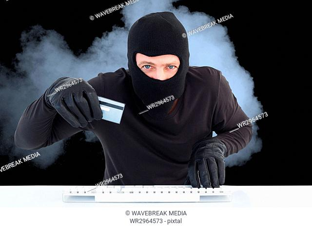 Hacker wearing hood is holding a credit card in the smoke against black background
