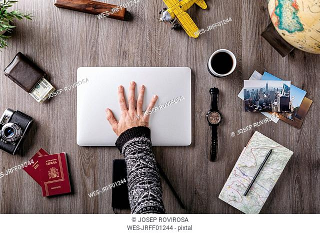 Overhead view of man's hand and travel items on table