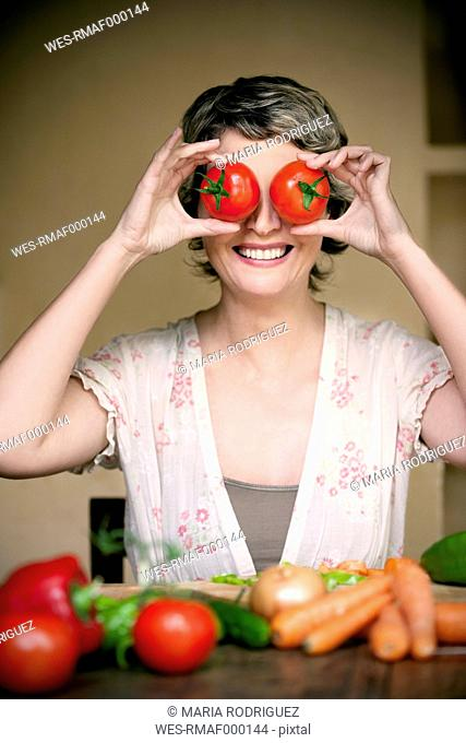 Portrait of smiling woman with tomatoes on her eyes