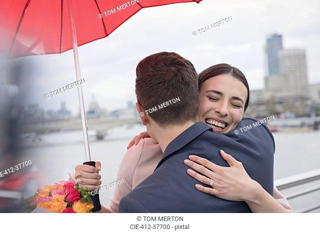 Smiling, affectionate couple with umbrella and flowers hugging on urban bridge, London, UK