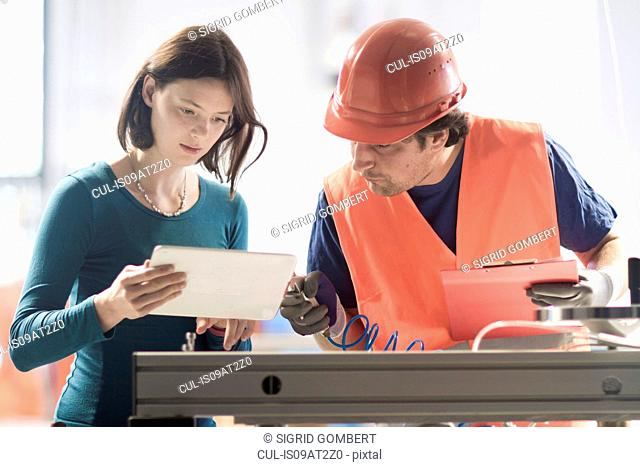 Male and female colleagues in industrial occupation using digital tablet
