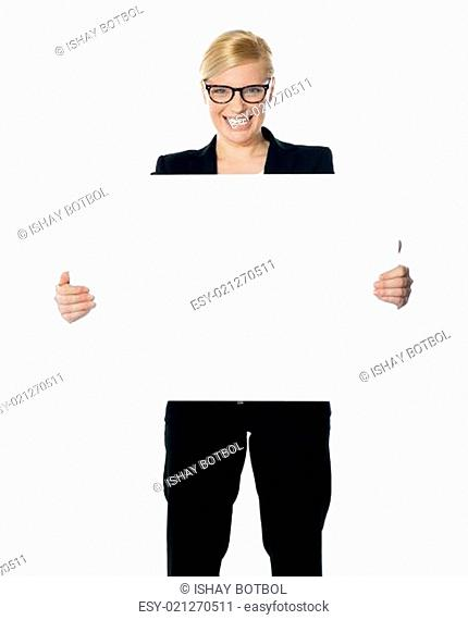 Attractive businesswoman holding blank advertising board