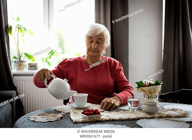 Senior woman pouring tea into cup from tea pot