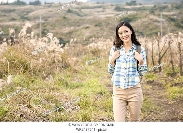 Young smiling female backpacker standing in silver grass field