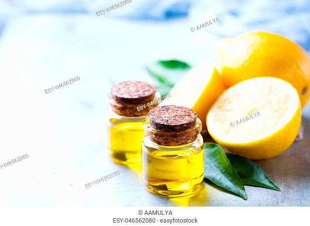 Health and beauty, still life concept. Organic essential lemon oil in a small glass jar with green leaves and yellow fruit on a white table