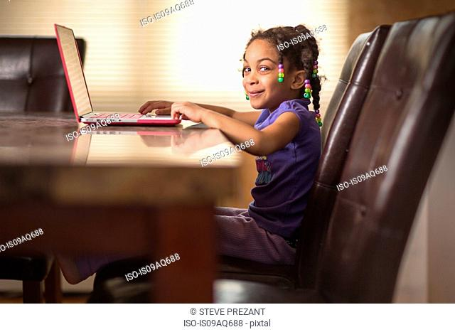 Portrait of cute girl at dining table using laptop