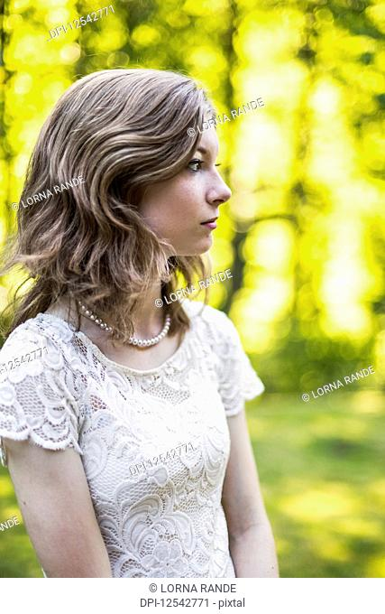 Portrait of a teenage girl in a lace dress standing in a park in autumn; Surrey, British Columbia, Canada