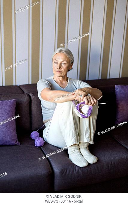Portrait of pensive senior woman sitting on the couch with knitting looking at distance