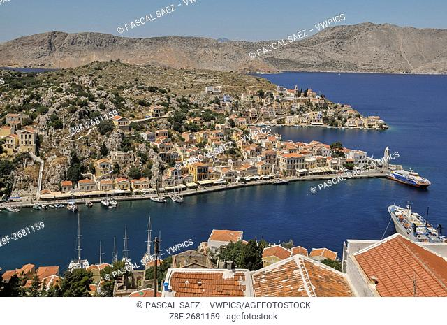 Partial view of Symi Town and its harbour seen from a hill above. Symi Town is the main settlement on the island of Symi, part of the Dodecanese island chain