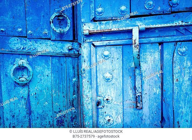 Antique wooden door with latch and doorknockers. Chaouen, Morocco