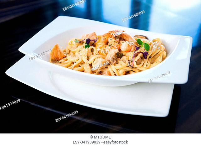 Creamy seafood pasta with salmon, shrimp, mussels and Grana Padano cheese