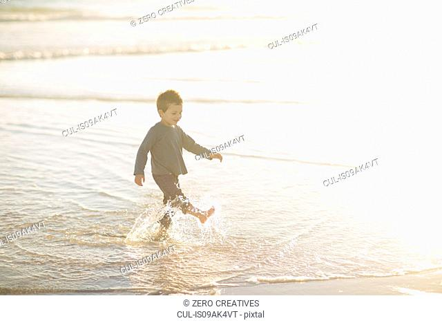Boy paddling and splashing in the sea
