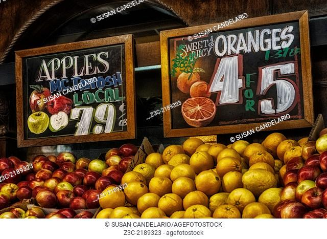 Fresh Mcintosh Apples and Sweet and Juicy Oranges at a farmers markets. The artsy advertising signs above the fruits invite customers to purchase the fruits