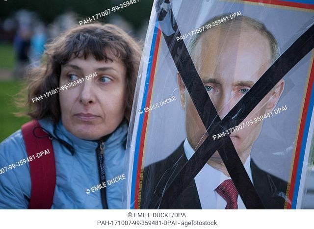 A woman holds up a crossed out portrait of Russian President Putin during a demonstration in the centre of St. Petersburg, Russia, 7 October 2017