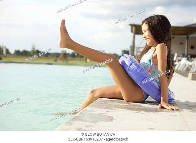 Girl sitting at the poolside